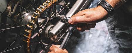 Mechanic working on Motocycle in mechanics garage. Repair service. authentic close-up shot 写真素材