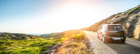 Coche de alquiler en España paisaje de montaña carretera al atardecer