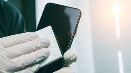 Person Cleaning mobile phone screen with disinfecting wipes for clean smartphone. COVID-19 Coronavirus outbreak contamination prevention concept. Archivio Fotografico