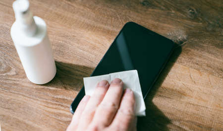 Person Cleaning mobile phone screen with disinfecting wipes for clean smartphone. COVID-19 Coronavirus outbreak contamination prevention concept.