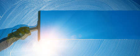 Window cleaner cleaning window with squeegee and wiper on a sunny day with a bright blue sky.