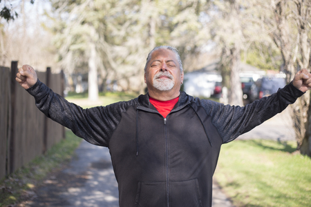 Attractive mature man with arms up toward the sky.