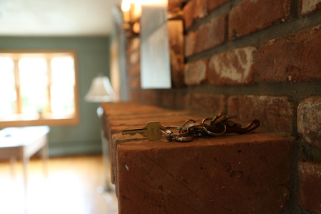 Side angle of a red brick fireplace in a living space with keys on mantle.