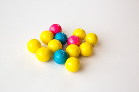 Colorful gumballs on a white background with selective focus.