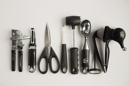 Black and steel kitchen gadgets shot overhead on a granite counter top.