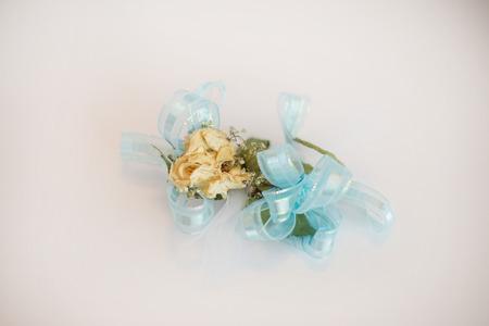 Rose Handgelenk Corsage mit blauem Band auf weißem Hintergrund.