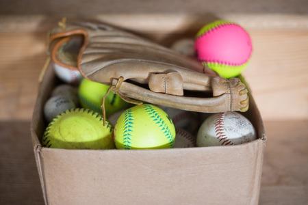 A box full of baseballs and a baseball glove.