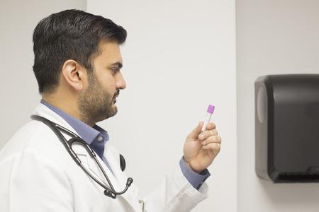 Doctor wearing blood test tubes.