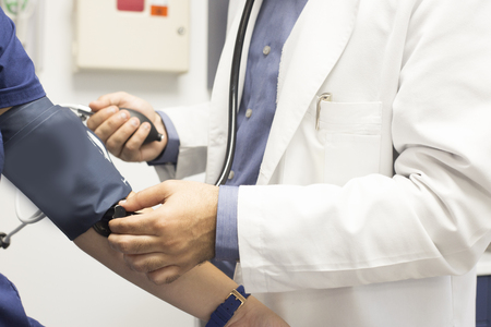 A medical doctor takes a patient's blood pressure.
