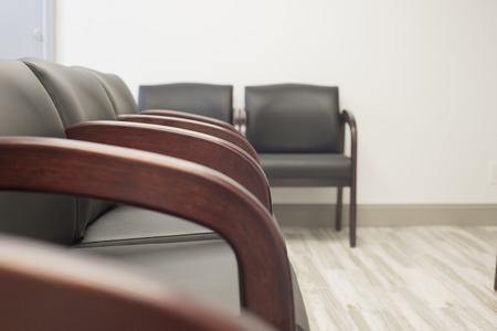 A row of black leather seats in an empty waiting room.