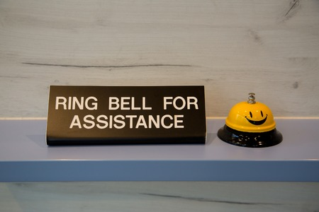 Ring bell for assistance sign next to a yellow reception bell.