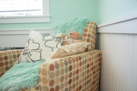 Baby nursery chair with blanket, pillow and teddy bear 免版税图像