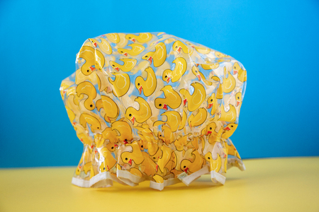 A yellow ducky shower cap shot on a colorful background. Stock Photo