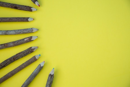 A row of colorful wood pencils on bright background