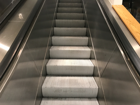 A sliver escalator with nobody at a mall.