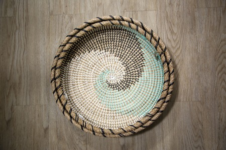 Empty basket shot overhead, from top, isolated on wood background.