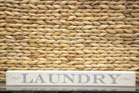 Laundry sign in front of textile texture of Hyacinth  or Rattan basket.