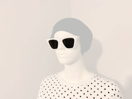 Mannequin wearing a hat and sunglasses on a modern realistic pop art style setting.