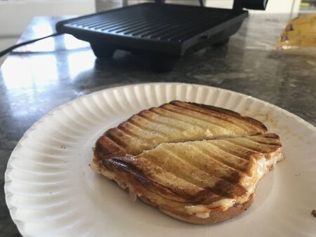 Grilled cheese sandwich on a white plate on a white and gray table. Imagens