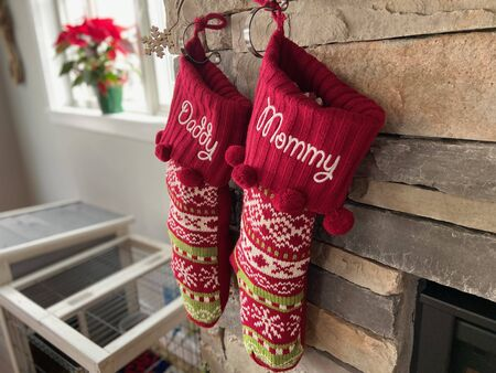 Mommy and Daddy Christmas stockings hanging on a fireplace mantle. Stock Photo