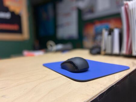 Computer mouse and mouse pad on a wooden desk.