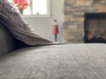 Gray couch with cozy blanket with blurred out background.