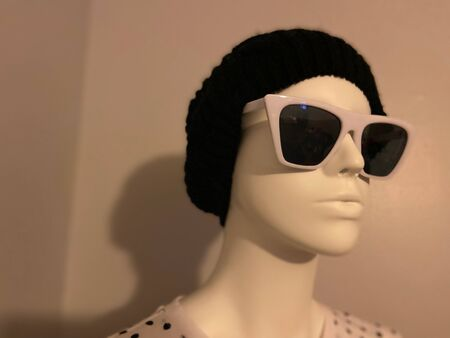 Transgender mannequin with modern, hip hat, sunglasses, and shirt.