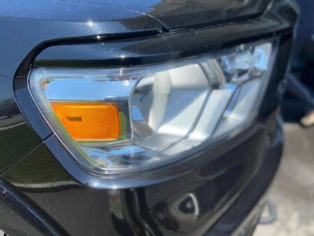 Front headlight and signal of a black pick up truck.