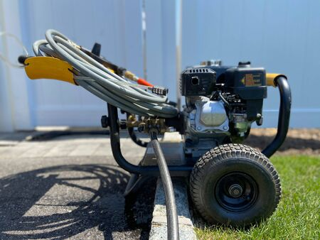Side angle view of a power washer on a sunny day without anyone in the shot.