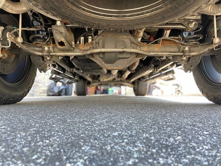 Undercarriage of a truck on a sunny day.