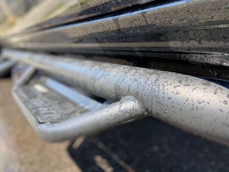 Truck step rail on a wet, black pick up truck.