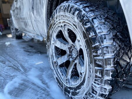 A truck tire with soapy suds all over it on a sunny day. Imagens