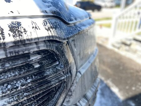 A truck with soapy suds all over it on a sunny day.