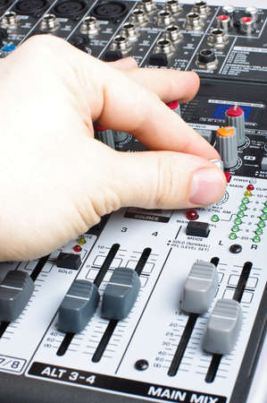 Male hand adjusting audio mixer desk photo