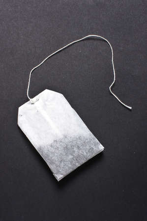 Flat teabag on the dark background without label