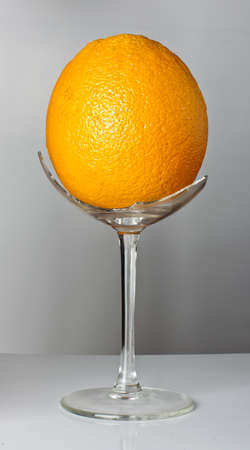 Orange in the broken wine glass on the grey background