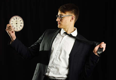 Man in black suit holding clock and tie Stock Photo