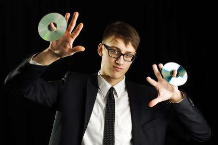 Young man in suit holding two compact discs photo