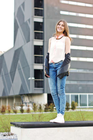 estilo urbano: La mujer joven de estilo urbano lindo que se coloca en el banco