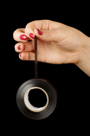 Female hand holding black gaffer tape roll photo