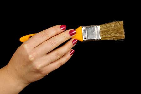 Female hand holding paintbrush isolated on the black background photo