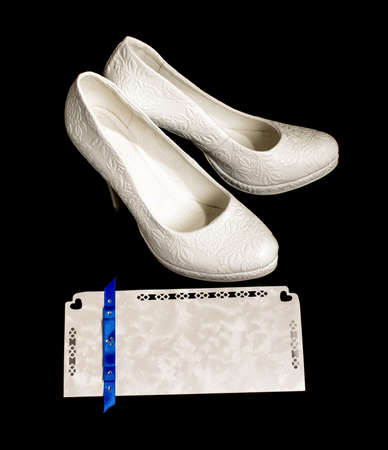 Pair of bride shoes and wedding invitation photo