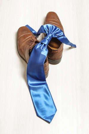 Blue tie and brown shoes on the wooden floor photo