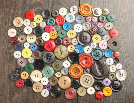 Pile of buttons on the wooden table
