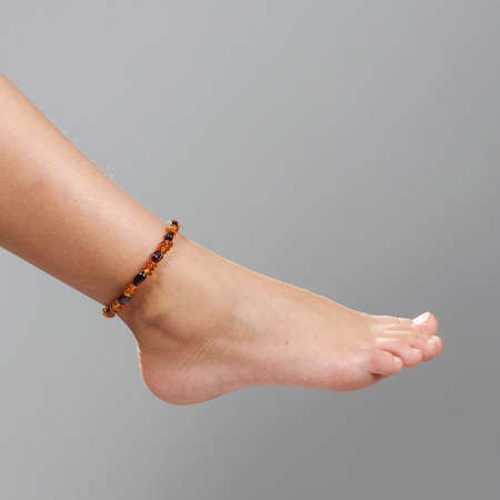 Girl foot isolated on the grey background
