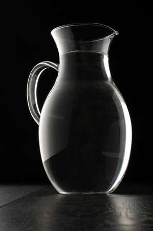 Glass water jug isolated on the black background photo