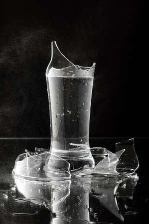 smithereens: Studio lit broken glass filled with water isolated Stock Photo