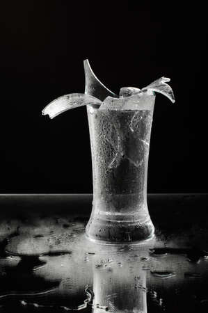 smithereens: Shattered beer glass isolated on the dark background Stock Photo
