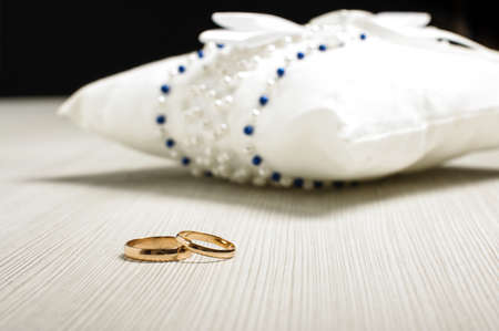 Pair of wedding rings in front of luxury cushion on the floor
