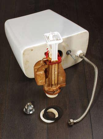 Dismantled toilet flushing mechanism on the dark background photo